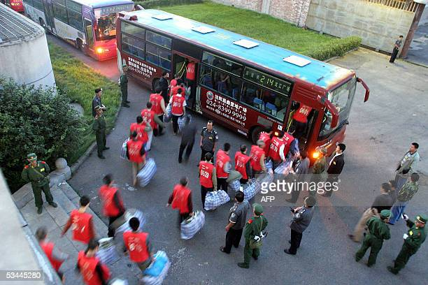A group of Chinese prisoners board a bus under guard as they move to a newly constructed prison in Shenyang in northeastern China's Liaoning province...