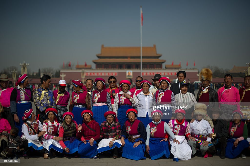 A group of Chinese tourists from Yunan province pose for a photo on Tiananmen Square prior to the opening session of the Chinese People's Political Consultative Conference (CPPCC) at the Great Hall of the People in Beijing on March 3, 2013. Thousands of delegates from across China meet this week to seal a power transfer to new leaders whose first months running the Communist Party have pumped up expectations with a deluge of propaganda. AFP PHOTO / Ed Jones
