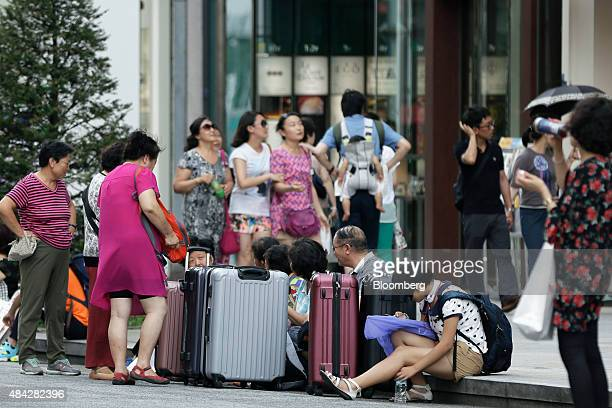 A group of Chinese tourists sit with their suitcases in the Ginza district of Tokyo Japan on Sunday Aug 16 2015 Japan's economy contracted last...