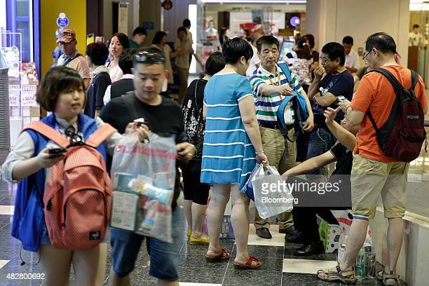 A group of Chinese tourists stand with shopping bags at the Canal City Hakata commercial complex in Fukuoka Japan on Friday July 24 2015 Four million...