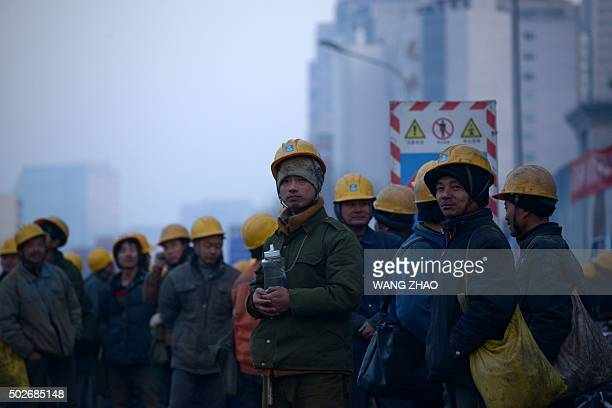 A group of Chinese workers wait for a shuttle bus outside a construction site in Beijing on December 28 2015 AFP PHOTO / WANG ZHAO / AFP / WANG ZHAO