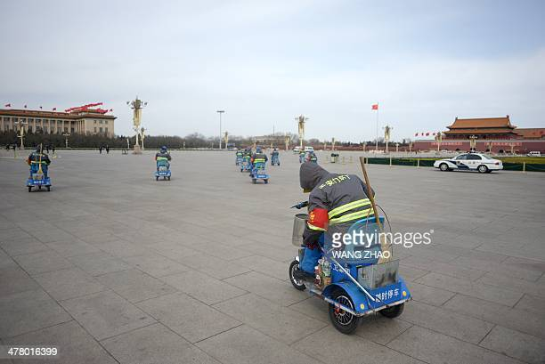 A group of cleaners clean the ground as they ride tricycle after the closing session of the Chinese People's Political Consultative Conference on the...