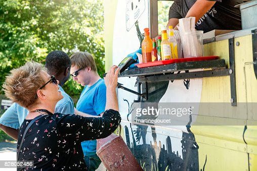 Group of clients around a food truck in a park. : Stock Photo