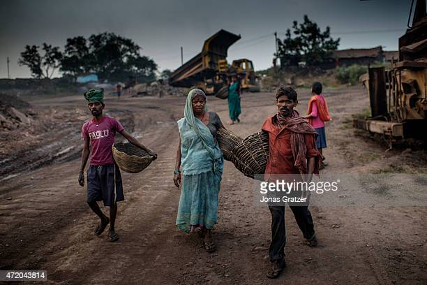 A group of coal mine workers are carrying their baskets and walking down the road in Jharia Jharia in India's eastern Jharkand state is literally in...