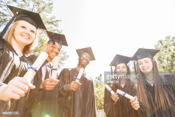 Group of college, high school students with diplomas at graduation.