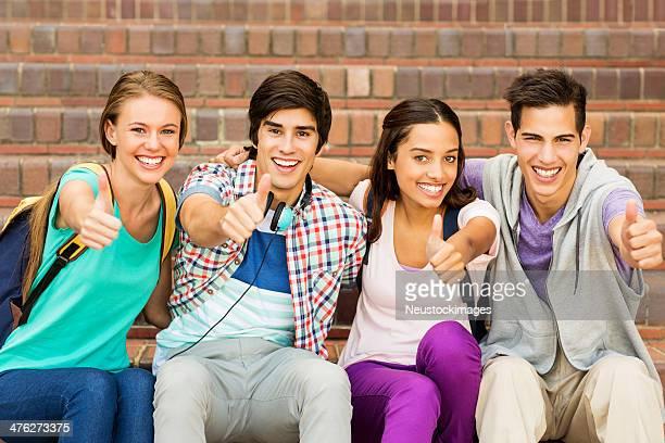 Gruppe von Studenten Gestikulieren Daumen hoch zusammen auf dem Campus