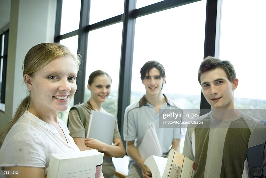 Group of college students standing around, holding books and binders, smiling at camera : Stock Photo