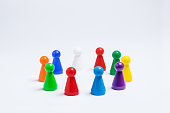 Group of colored pawns arranged in a circle on a white background