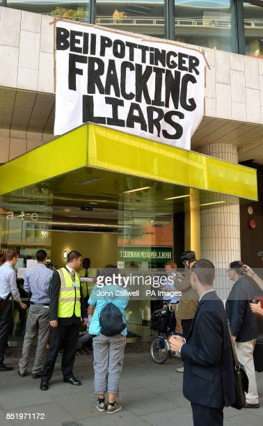 A group of commuters stand and take pictures of antifracking demonstrators as they sit with their hands superglued to each other at the offices of...