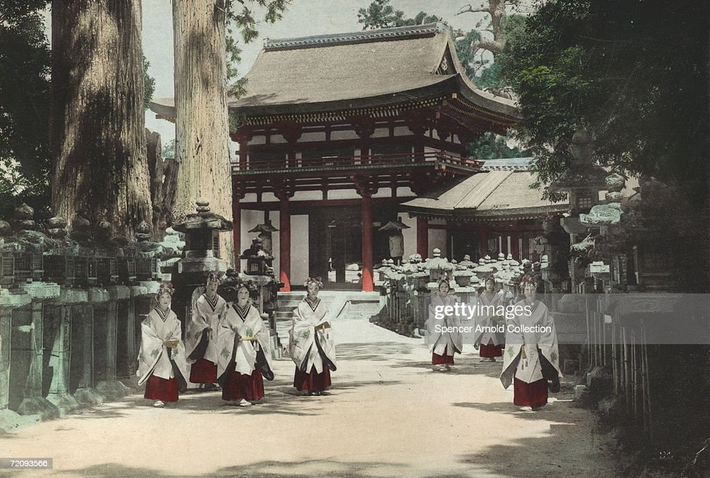 A group of consecrated maidens at the entrance to the Kasuga Shrine in Nara Japan circa 1880