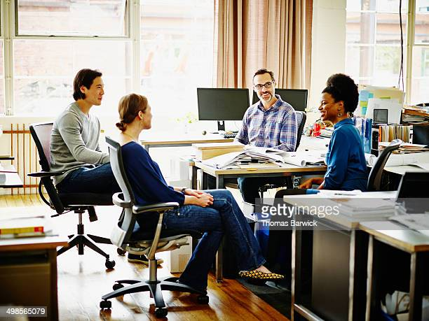 Group of coworkers in office discussing project