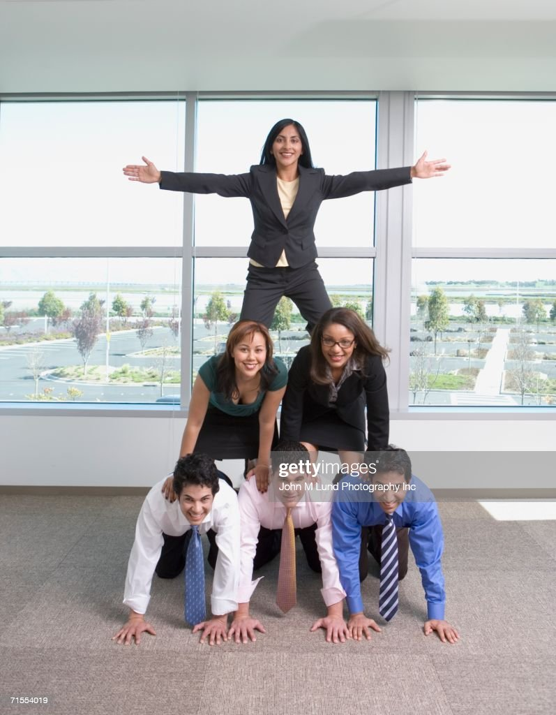 Group of coworkers in pyramid trust exercise