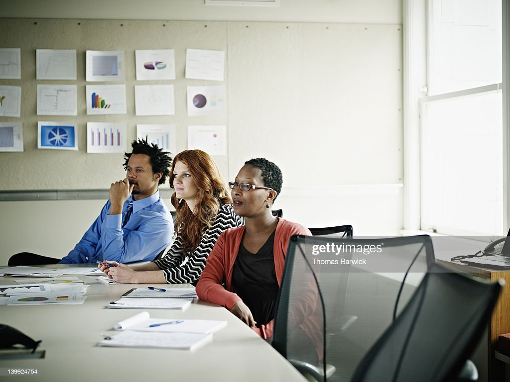 Group of coworkers listening at conference table : Stock Photo