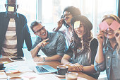 Joking group of diverse young adult coworkers playing with sticky notes on their faces as a distraction during a meeting