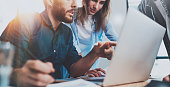 Group of coworkers sitting at the wooden table and working together on new startup project in modern loft office.Horizontal.Blurred background.Cropped