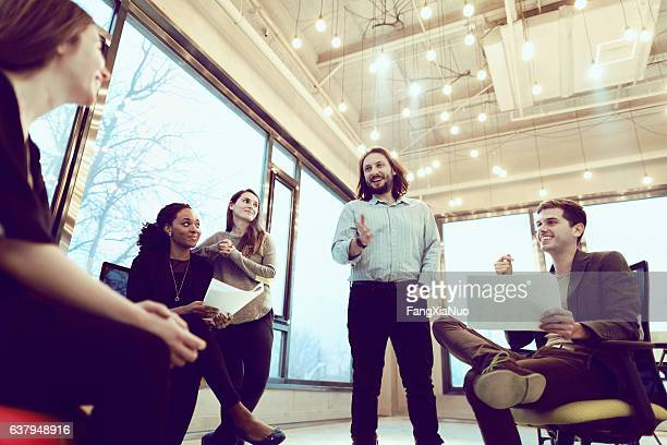 Group of coworkers talking together in studio environment