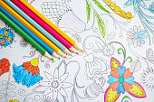 Multi-color crayons on open page of coloring book