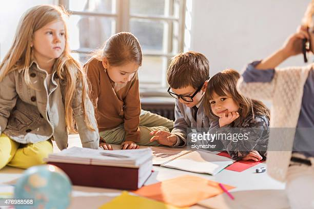 Group of creative children reading documents together.