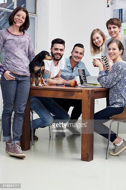 Group of creative professionals with dog at table