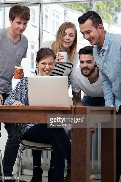 Group of creative professionals with laptop at table