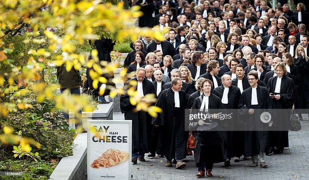 A group of criminal defense lawyers takes part in a protest on their way to the Court house in Amsterdam, The Netherlands, on November 11, 2013. The lawyers are demonstrating against the austerity plans of the Dutch Undersecretary of Justice, Fred Teeven. AFP PHOTO / ANP / KOEN VAN WEEL