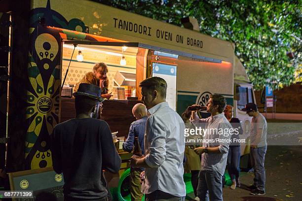 Group of customers at food truck at night