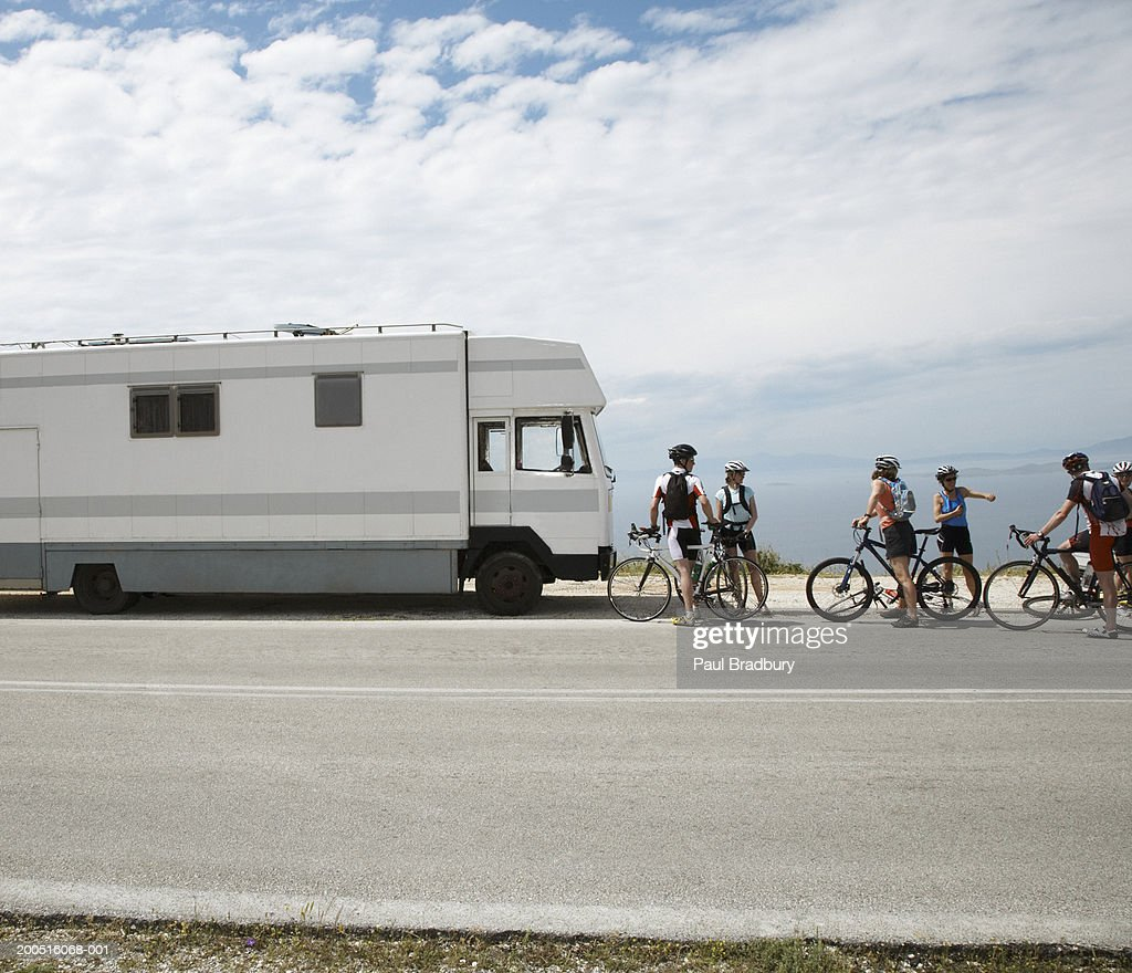 Group of cyclists on roadside by motor home : Stock Photo