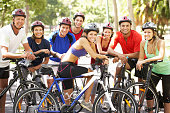 Group Of Cyclists Resting During Cycle Ride Through Park Smiling