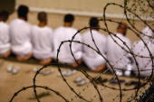 A group of detainees kneels during an early morning Islamic prayer in their camp at the US military prison for 'enemy combatants' on October 28 2009...