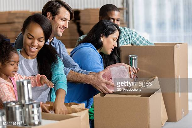 Group of diverse volunteers pack boxes during food drive