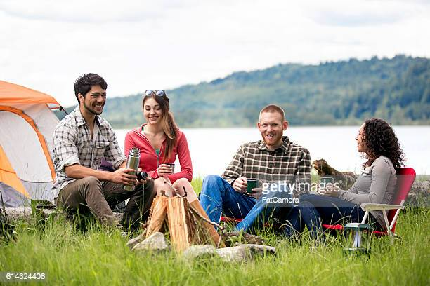 Group of diverse young adults talking around a campsite