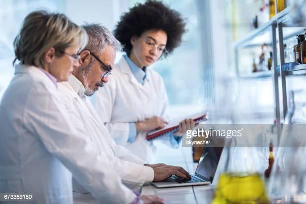 Gruppe von Ärzten, medizinische Daten auf Laptop im Labor zu analysieren.