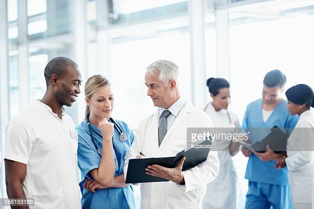 Group of doctors discussing patient's report