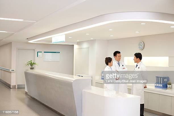 A group of doctors talking behind a deask