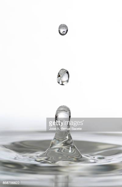 Group of drops on line suspended in the air, falling down on a water surface that forms figures and abstract forms, on a white background