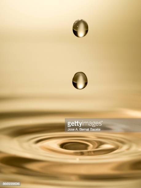 Group of drops on line suspended in the air, falling down on a water surface that forms figures and abstract forms, on a gold-colored background
