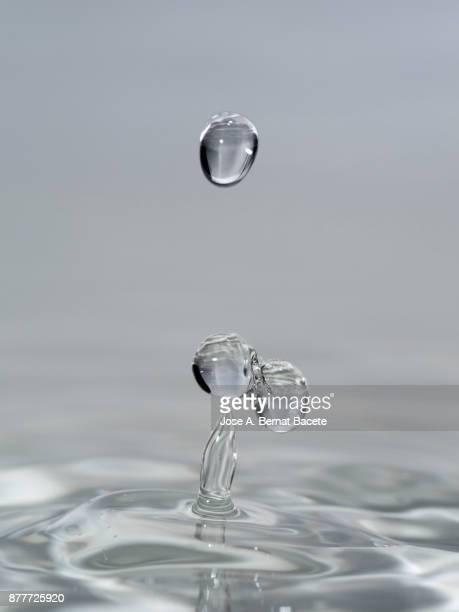 Group of drops on line suspended in the air, falling down on a water surface that forms figures and abstract forms, on a gray background