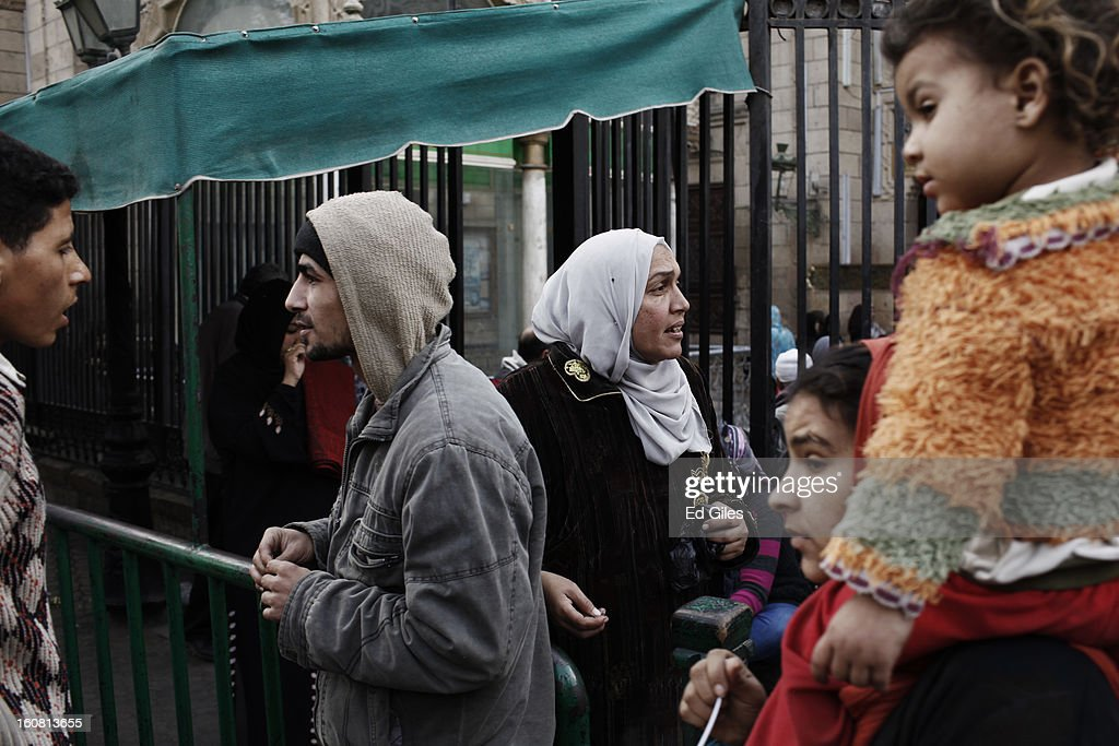 A group of Egyptian people observe a passing march against sexual harassment at the Seiyda Zeinab Mosque, on February 6, 2013 in Cairo, Egypt. Around a thousand Egyptian men and women marched through the Egyptian capital to the city's iconic Tahrir Square on Wednesday to demonstrate against the continuing problem of sexual harassment of Egyptian and foreign women during protests across Egypt. (Photo by Ed Giles/Getty Images).