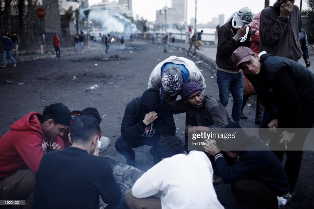 A group of Egyptian protester affected by exposure to tear gas gather beside a fire during clashes between protesters and Egyptian riot police near Tahrir Square on January 28, 2013 in Cairo, Egypt. Violent protests continued across Egypt three days after the second anniversary of the Egyptian Revolution that overthrew former President Hosni Mubarak and two days after 21 men were sentenced to death in connection with the deaths of 74 football fans during riots at Port Said stadium one year ago.
