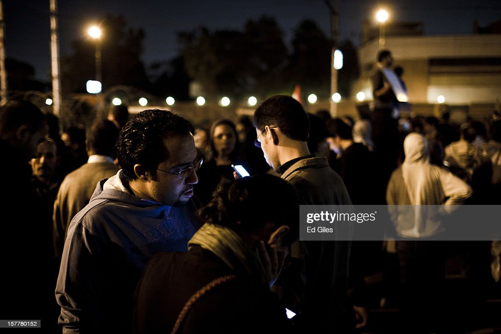 A group of Egyptian protesters look at mobile phones during a demonstration in front of Egypt's Presidential Palace, after violent clashes the previous night, on December 6, 2012 in Cairo, Egypt. At least five people were reported killed in the Cairo suburb of Heliopolis late on December 5 after thousands of protesters from groups both supporting and against President Morsi converged on the Presidential Palace, following large anti-government demonstrations in front of the palace on December 4. Anti-Morsi protesters continue to demonstrate across Egypt against the country's draft constitution, rushed through parliament in an overnight session on November 29. The country's new draft constitution, passed by a constitutional assembly dominated by Islamists, will go to a referendum on December 15.
