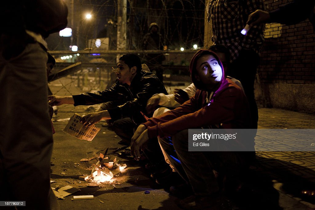 A group of Egyptian protesters sit by a fire during a demonstration in front of Egypt's Presidential Palace, after violent clashes the previous night, on December 6, 2012 in Cairo, Egypt. At least five people were reported killed in the Cairo suburb of Heliopolis late on December 5 after thousands of protesters from groups both supporting and against President Morsi converged on the Presidential Palace, following large anti-government demonstrations in front of the palace on December 4. Anti-Morsi protesters continue to demonstrate across Egypt against the country's draft constitution, rushed through parliament in an overnight session on November 29. The country's new draft constitution, passed by a constitutional assembly dominated by Islamists, will go to a referendum on December 15.
