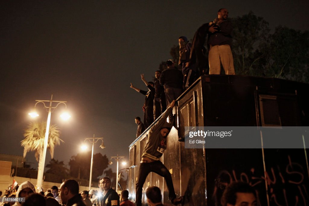 A group of Egyptian protesters stand on top of a riot police truck left behind by security forces during a protest against Egyptian President Mohammed Morsi at the Presidential Palace on December 4 in in Cairo, Egypt. Thousands of protesters converged on the Presidential Palace in the Cairo suburb of Heliopolis on Tuesday evening to demonstrate against the country's draft constitution that was rushed through parliament in an overnight session on November 29. Protesters and police briefly clashed outside the Presidential Palace before riot police retreated inside the palace grounds. The country's new draft constitution, passed by a constitutional assembly dominated by Islamists, will go to a referendum on December 15.