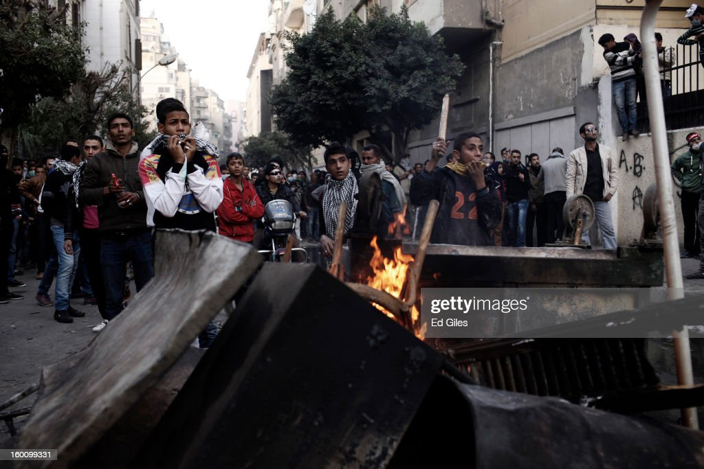 A group of Egyptian protesters take cover from nearby Egyptian riot police during a protest following the announcement of the death penalty for 21 suspects in connection with a football stadium massacre last year, on January 26, in Cairo, Egypt. Protests have continued across Egypt after a verdict was announced in a case over the deaths of more than seventy fans of Egypt's Al-Ahly football club in a stadium massacre on February 1, 2012, in the northern city of Port Said, during a brawl that began minutes after the final whistle of a match between Al-Ahly and opposing side, Al-Masry. 21 fans of the opposing side, Al-Masry, were given the death penalty in the court case, a verdict that must now be approved by Egypt's Grand Mufti. The verdict was handed down during a period of high tension across Egypt, one day after the second anniversary of the beginning of Egypt's 2011 revolution that overthrew former President, Hosni Mubarak.
