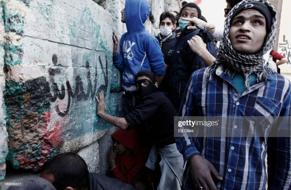 A group of Egyptian protesters take shelter behind a stone wall during clashes with riot police in Tahrir Square on January 25, in Cairo, Egypt. Thousands of protesters converged on the capital's iconic Tahrir Square on Friday to mark the second anniversary of the overthrow of former President Hosni Mubarak's regime. (Photo by Ed Giles/Getty Images).