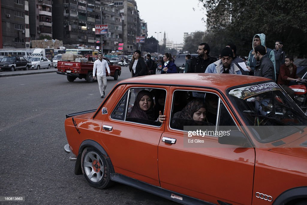 A group of Egyptian women in a car observe a passing march against sexual harassment at the Seiyda Zeinab Mosque, on February 6, 2013 in Cairo, Egypt. Around a thousand Egyptian men and women marched through the Egyptian capital to the city's iconic Tahrir Square on Wednesday to demonstrate against the continuing problem of sexual harassment of Egyptian and foreign women during protests across Egypt. (Photo by Ed Giles/Getty Images).