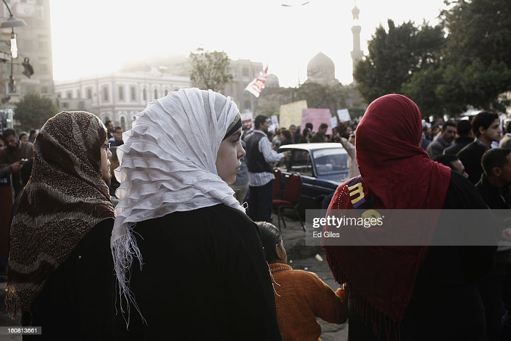 A group of Egyptian women observe a passing march against sexual harassment at the Seiyda Zeinab Mosque, on February 6, 2013 in Cairo, Egypt. Around a thousand Egyptian men and women marched through the Egyptian capital to the city's iconic Tahrir Square on Wednesday to demonstrate against the continuing problem of sexual harassment of Egyptian and foreign women during protests across Egypt. (Photo by Ed Giles/Getty Images).