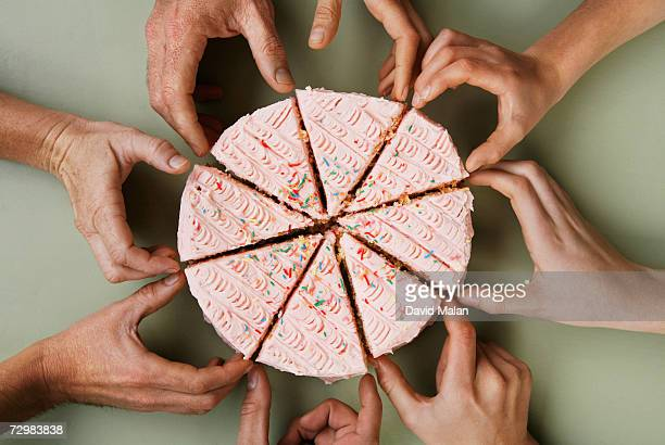 Group of eight people reaching for slice of cake, close-up, overhead view