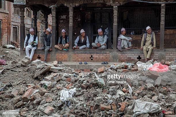 A group of elderly men chat near a pile of debris on July 29 2015 in Bhaktapur Nepal Three months after the earthquake that hit Nepal on April 25th...