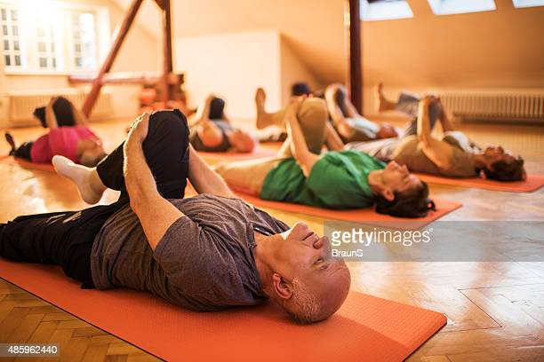 Group of elderly people doing relaxation exercises in health club.