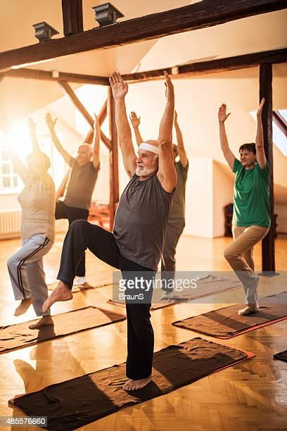Gruppe der älteren Menschen Training mit erhöhter Armen und Beinen.